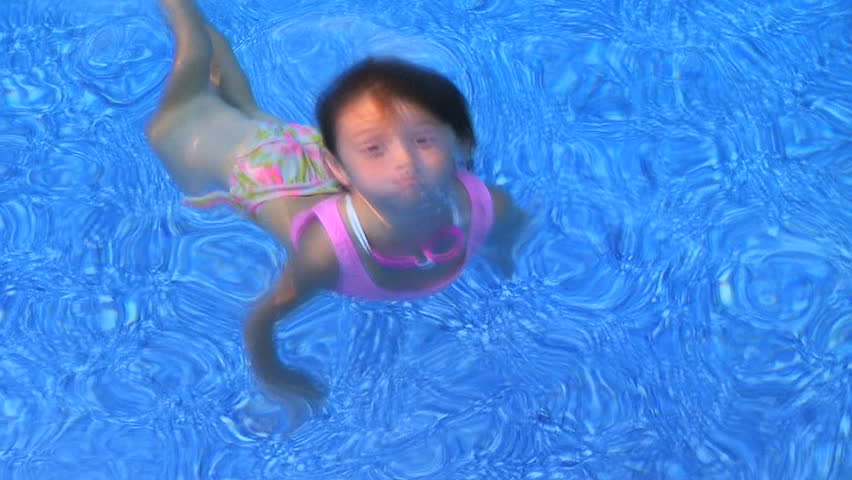 Little girl swimming underwater  in clear blue water and coming up smiling.
