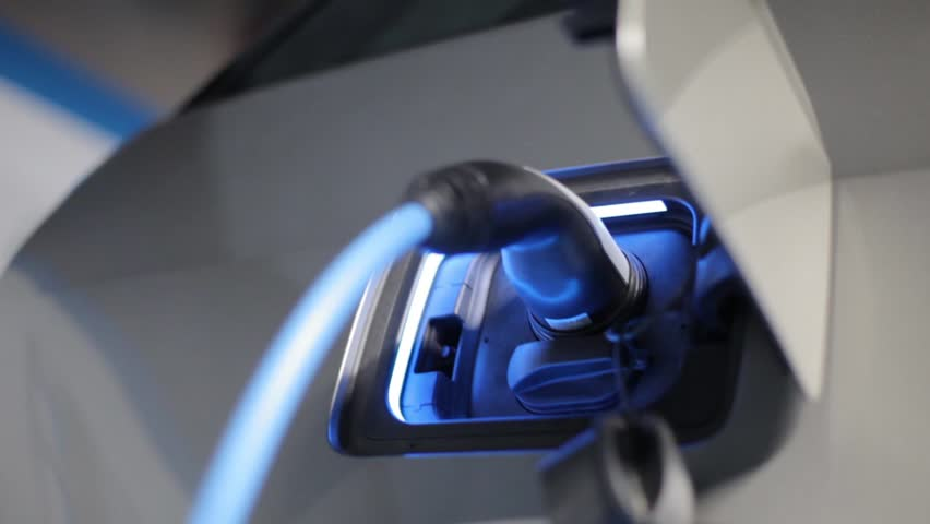Color footage with a plug charging an electrical car.