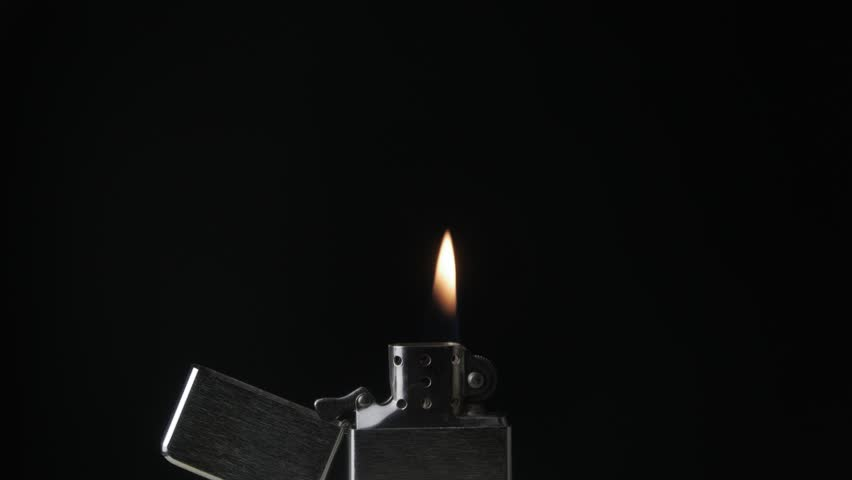 Open metal lighter zippo with flame on black background
