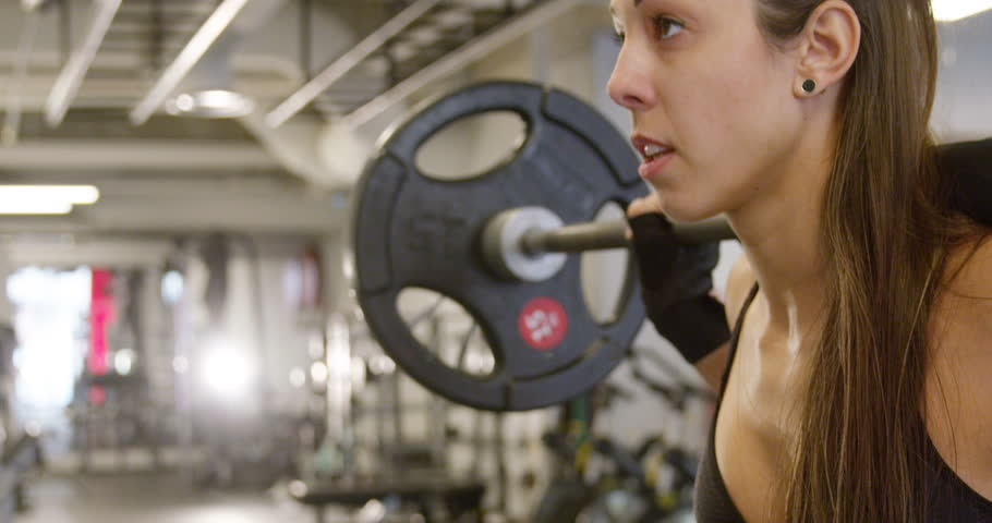 Motivated strong woman doing squats workout with heavy weights   Shutterstock HD Video #34592146
