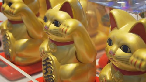 HULHUMALE, MALDIVES - CIRCA DEC 2016: The maneki-neko (beckoning cat) is a common Japanese figurine (lucky charm. talisman) at a Shop counter