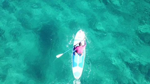 Aerial drone video of man in a paddle surf board known as Sup surfing in turquoise clear waters