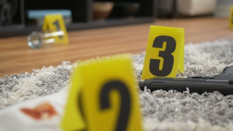 Evidence and weapon on floor of crime scene with yellow evidence markers. Tracking shot.