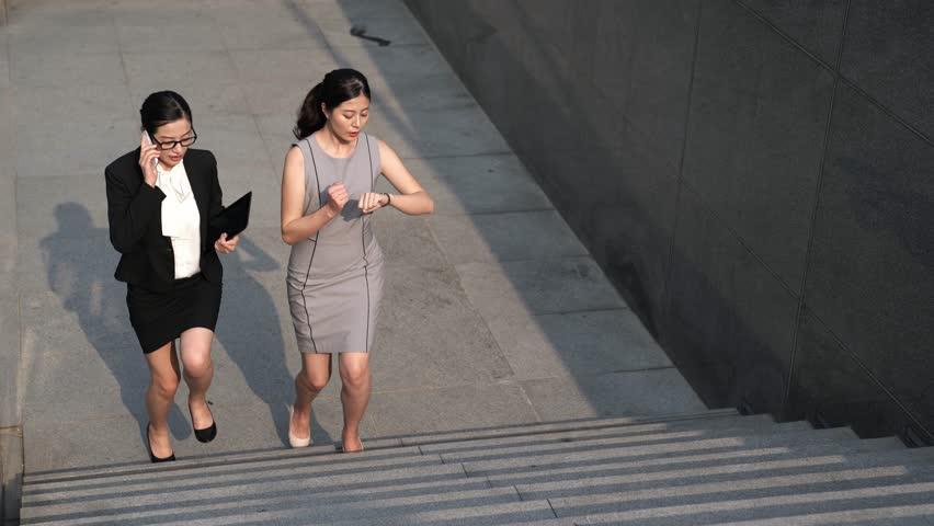 Two Asian beautiful businesswomen on hurry walking on stairs. one talking on the phone and the other one look at watch running on the stairway. | Shutterstock HD Video #34608826