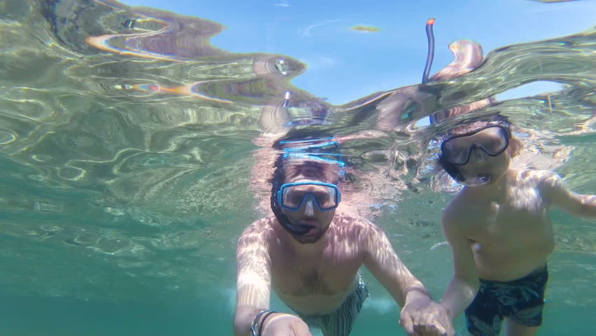 Father and son with flippers, mask, snorkel and a selfie stick swimming in the sea, gopro underwater footage