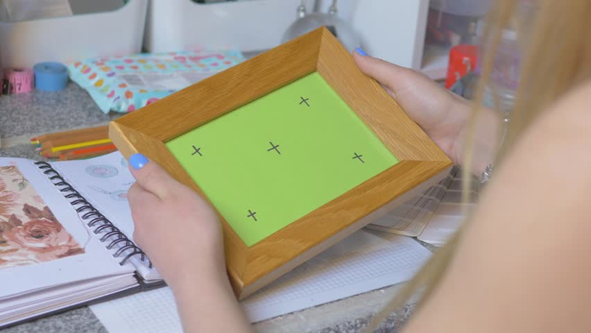 Female hands holding photo frame with Green Screen and tracking markers. Memories concept.