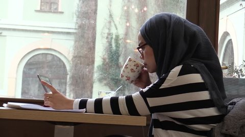 OLOMOUC, CZECH REPUBLIC, DECEMBER 17, 2017: A woman studying student studying text from ipad and drinking quality coffee and head on hijab traditional scarf of Muslim religious women