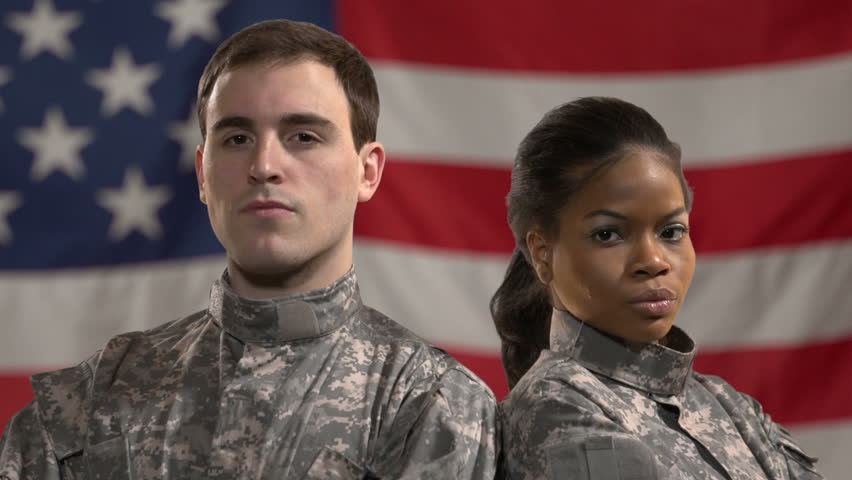 Male and female soldiers standing in front of American Flag. Shot in green screen, flag was added later. Close up