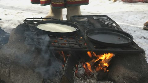 Cooking traditional russian pancakes on frying pan on bonfire