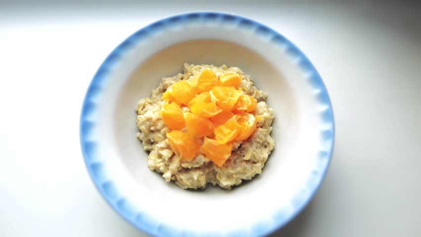 Closeup shot of healthy breakfast, oatmeal porridge with milk and mandarins. Oat flakes filled with milk in a faience dish on a white background. Organic food concept for strong muscles.