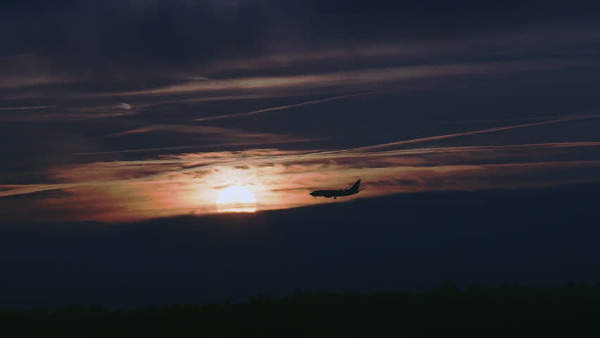 Silhouetted Airplane Flying In Front Of The Setting Sun Before Landing. | Shutterstock HD Video #34717822