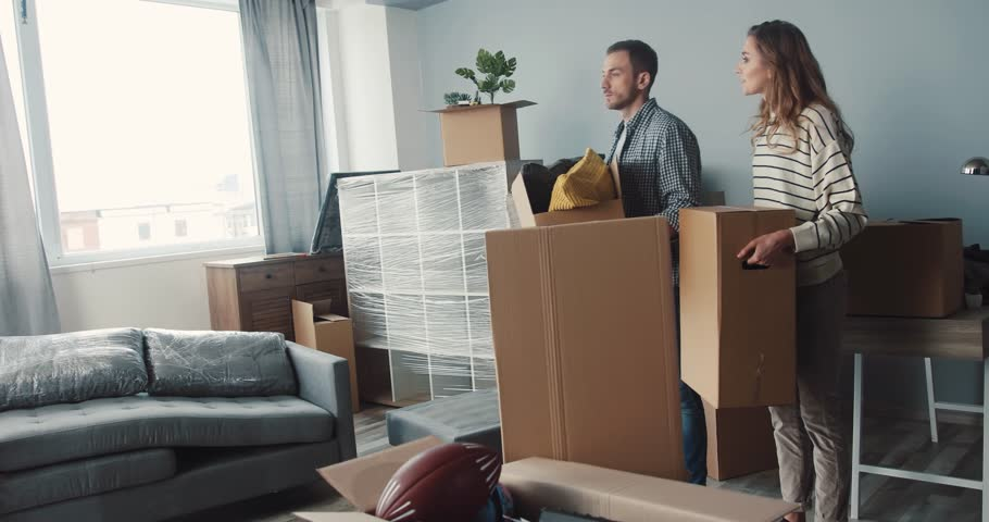 Young happy family couple with spaniel moving to new apartment. People in love putting boxes on floor. Smiling. | Shutterstock HD Video #34760866