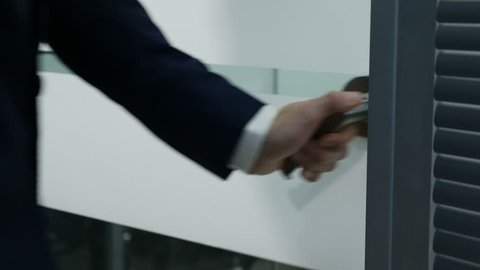 Business office life concept, Male hand opens glass door handle. Man in suit enter room. opening door in modern office. Shot in 4 k