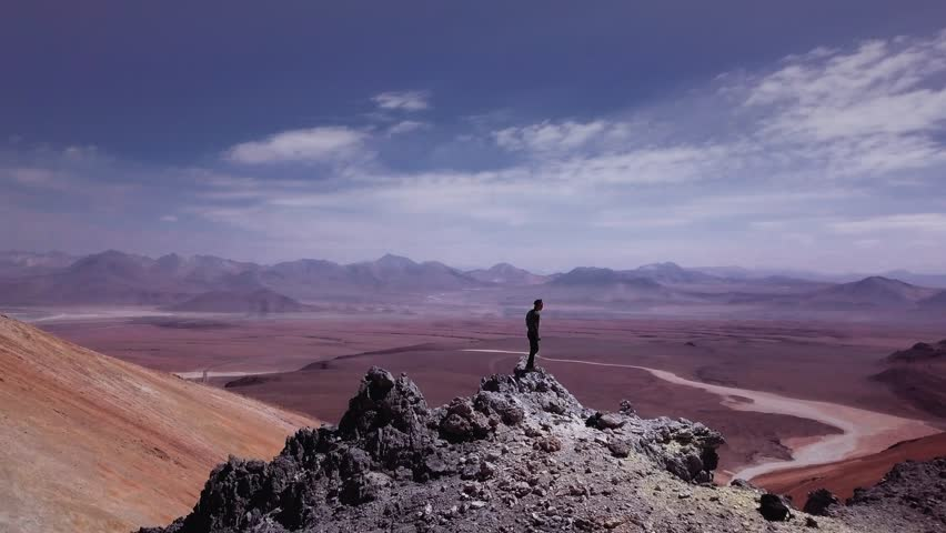 Male sky runner on summit of the colorful mountain chain on Atacama desert, 4k. Aerial view of a man standing on summit of a volcano peak.  | Shutterstock HD Video #34771246
