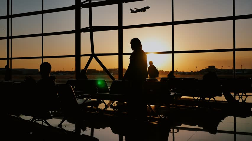 Silhouette of a tourist guy watching the take-off of the plane standing at the airport window at sunset in the evening. Travel concept, people in the airport.
