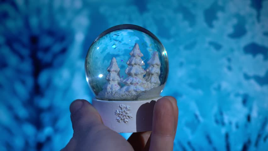 Hand moving a snow globe