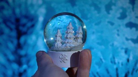 Hand moving a snow globe