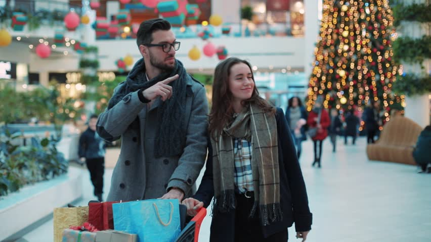 Close up lovely couple with Christmas present walk in a mall smiling feel happy shopper family woman tree christmas shopping man shop store portrait gift holiday shopping slow motion