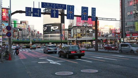 Tokyo, Japan - May 12 2017: Traffic in the crowded street in fron of the Kabukicho district of Shinjuku in Tokyo with the elevated railway tracks in the background in Japan capital city.