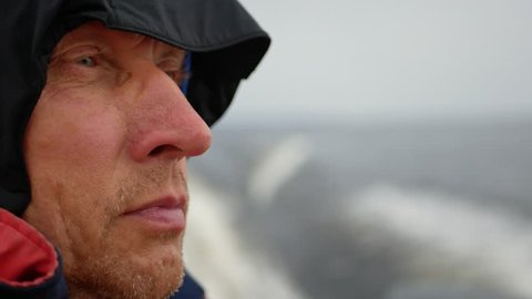 Close-up face of a man with a hood on his head. Fast speed floats on a boat on the sea, a strong wind is blowing and the boat is swinging on the waves. 3840x2160, 4k