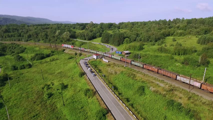 Freight train carries an electric locomotive by two-sided winding railway with railroad crossing  in the Ural Mountains - Aerial Photography, top view