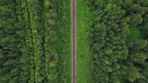 Empty straight single-way railways at summer sunny day in Ural Mountains in Russia, endless railway without train - aerial top view