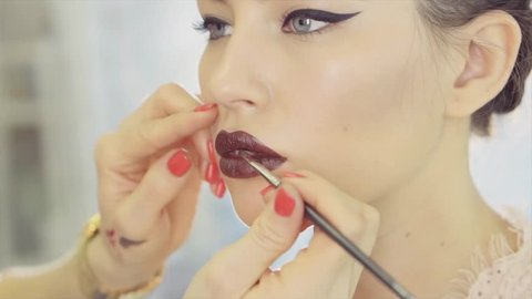 Female master of make-up is applying dark brown pomade on lips of customer. She is using professional cosmetic brush and withholding skin of face