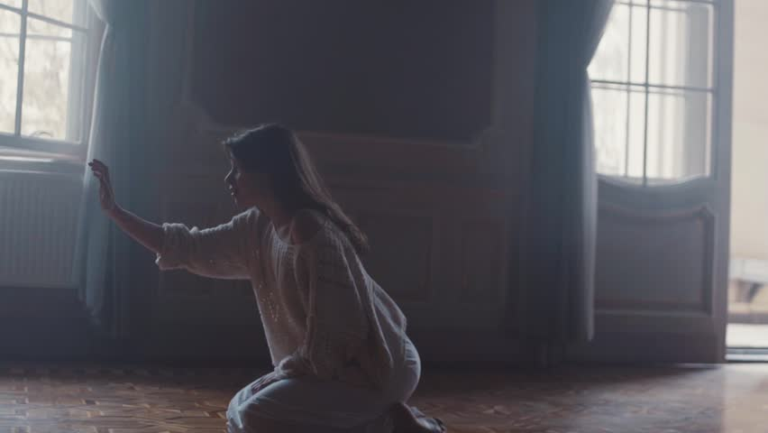 Young woman sits on her knees in a dark, old room with high ceiling, she reaches out her hand as trying to touch something. She strokes something in the air, she is shocked and scared, walks away | Shutterstock HD Video #34859596