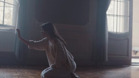 Young woman sits on her knees in a dark, old room with high ceiling, she reaches out her hand as trying to touch something. She strokes something in the air, she is shocked and scared, walks away