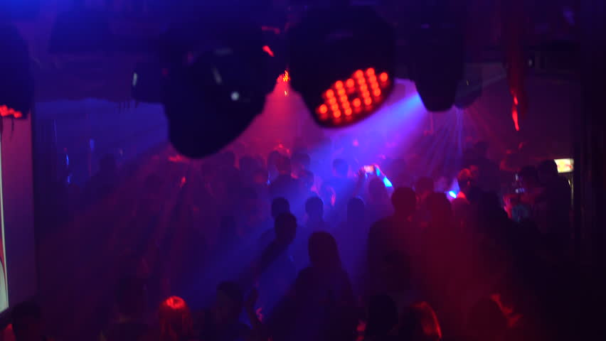 Interior view of modern spacious nightclub with flashing lights and people dancing to music.