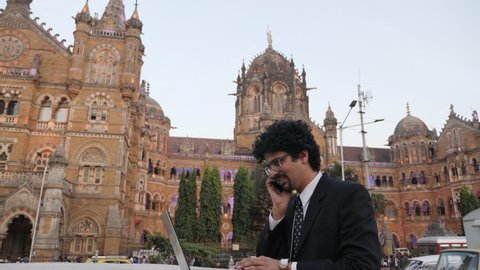 4k footage of office going young man using mobile phone, tablet, laptop in front of CST previously Victoria Terminus.