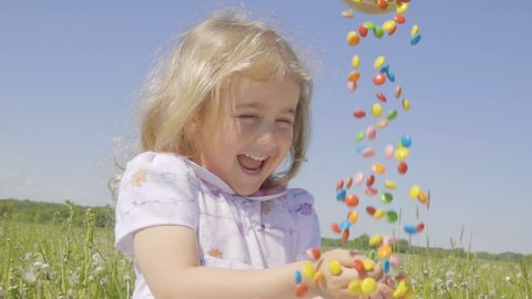 Cute little girl with pleasure catches multicolored candy falling from above. Joyful cheerful child laughing outdoors. Summer sunny day. Slow Motion.