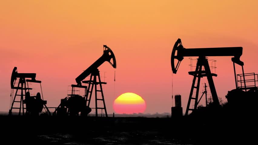 working oil pumps silhouette against timelapse sunrise