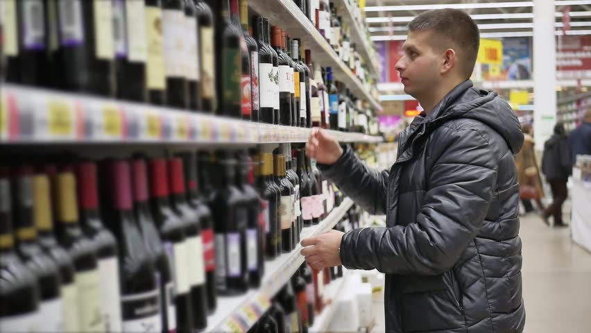 A young man chooses a wine at the supermarket. Difficult choice. Man is buying a bottle of alcohol at the supermarket. | Shutterstock HD Video #34909585
