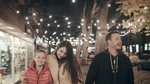 A happy family walks the evening in the city on holidays