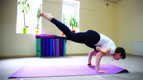 Beautiful girl of American appearance perform yoga exercises, young woman engaged in fitness studios. Room spacious and light, large windows in place, pots with flowers on windowsills, in corner drawn