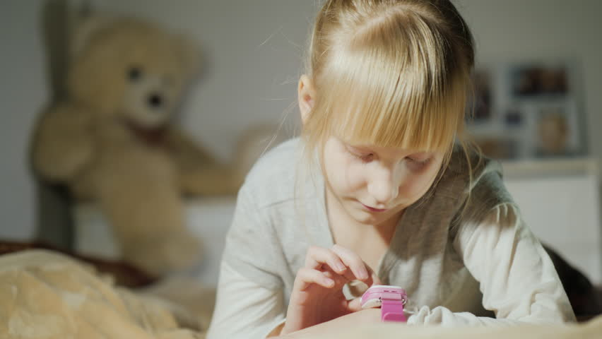 A girl is playing with a smart clock on her arm. Lying on the bed in the bedroom