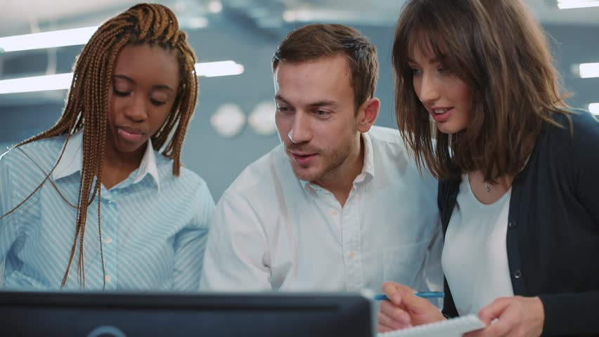 Young people of different nationalities standing near computer and looking at monitor, discussing something in beautiful modern office. Smiling. Indoors. | Shutterstock HD Video #34937734