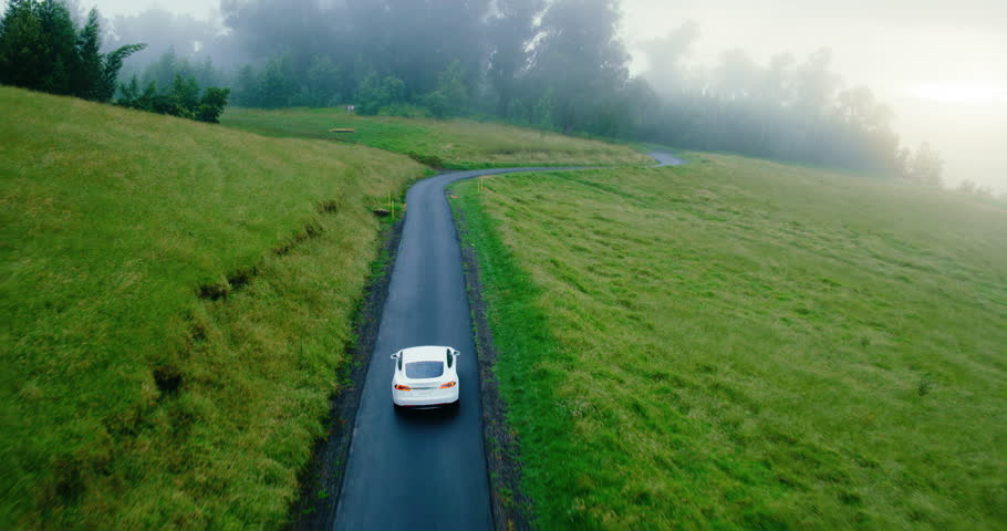 Cinematic aerial view of electric car driving on country road at sunset | Shutterstock HD Video #34949596