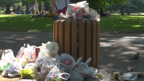 LONDON, JULY 30, 2013, Full garbage bin in town park, people food lunch waste in trash container litter by day