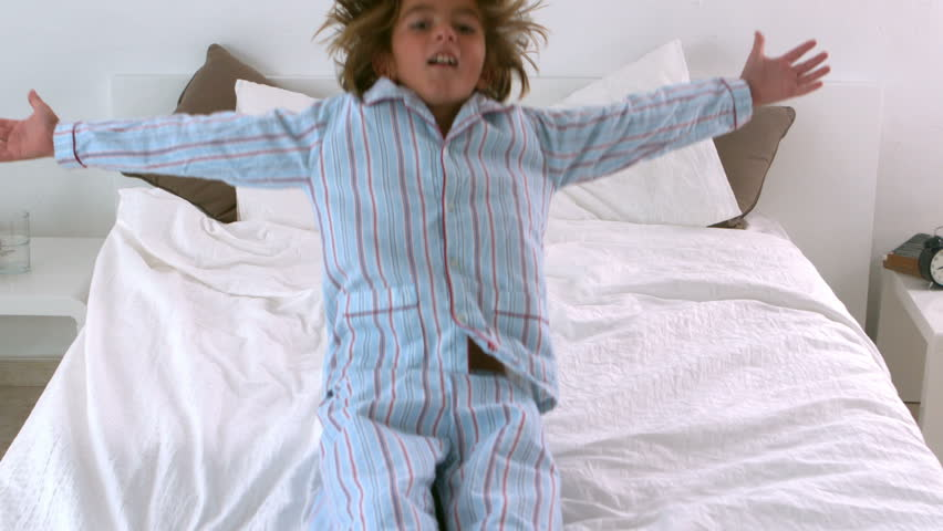 Little boy in pajamas jumping back onto bed in slow motion