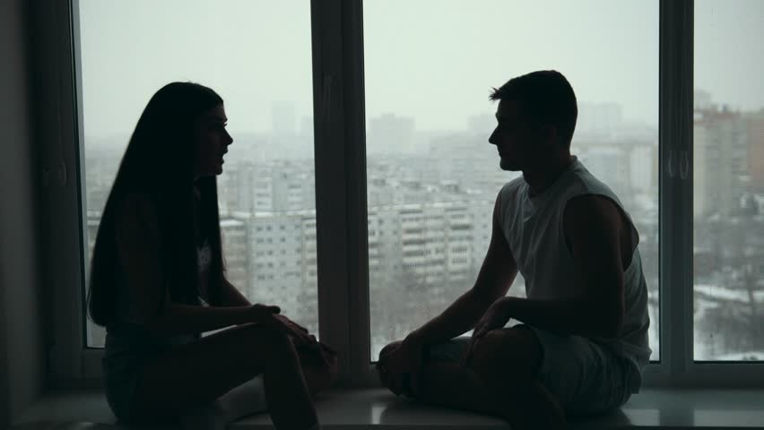 Young happy couple sitting on the windowsill, emotionally talking, arguing and gesticulating | Shutterstock HD Video #35007256
