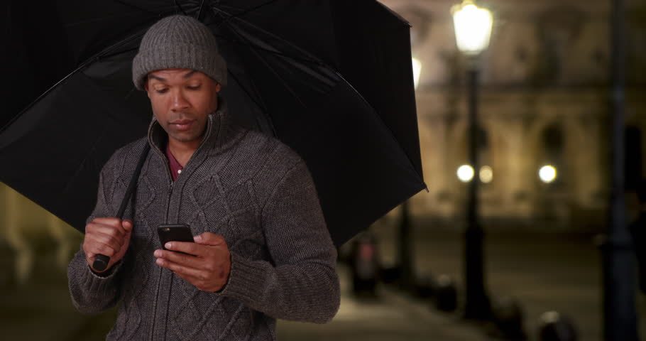 African-American male in Paris, France standing outside with an umbrella on a chilly night. Black young man in a sweater and beanie holding an umbrella outside. 4k | Shutterstock HD Video #35018116