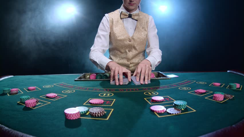 Dealer handling playing cards at a poker table. Smoke. Slow motion