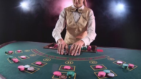Casino stickman woman distributes cards on the poker table top using cut card. Black background. Smoke. Slow motion