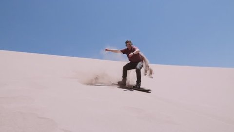 Man sandboarding at the Great Sand Dunes of the Dead Valley, Atacama desert. Slow motion