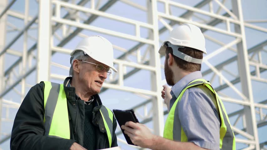 Construction Engineers Consult With Touchscreen Tablet For Building Development 4K. Planning Meeting Onsite.