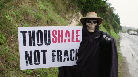 """Anti Fracking protester wearing Death costume at unconventional gas exploration demonstration. """"Thou shale not frack""""."""