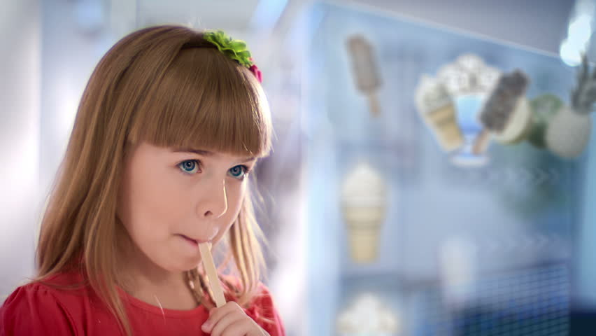 little girl selects dessert on touchscreen monitor