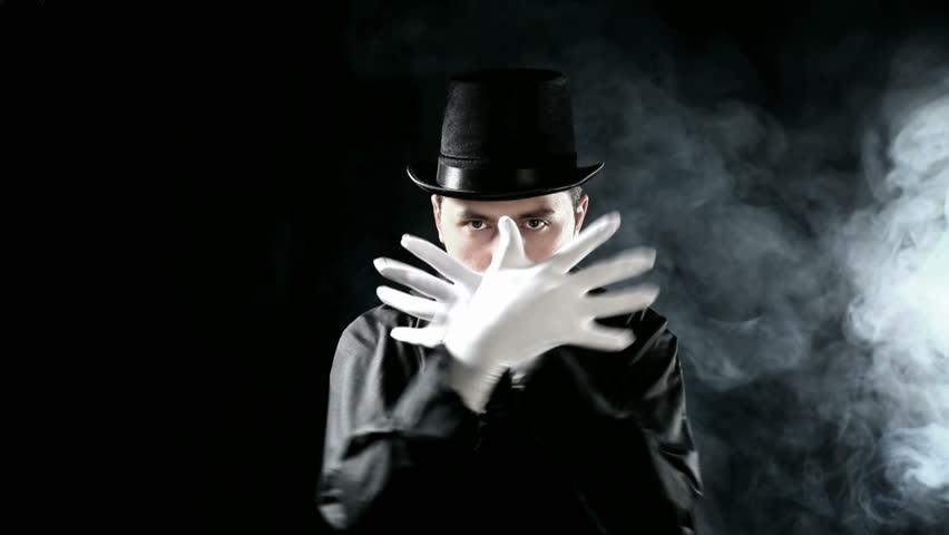 magician filmed on black background